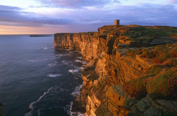 HeraldScotland: LOOKING OVER THE CLIFFS OF MARWICK HEAD AT SUNSET, WITH THE KITCHENER MEMORIAL VISIBLE IN THE BACKGROUND, MAINLAND, ORKNEY..Pic: Iain Sarjeant / VisitScotland ............***VISITSCOTLAND USE ONLY TO PROMOTE ORKNEY, NO THIRD PARTY USE WITHOUT CONTACTING V