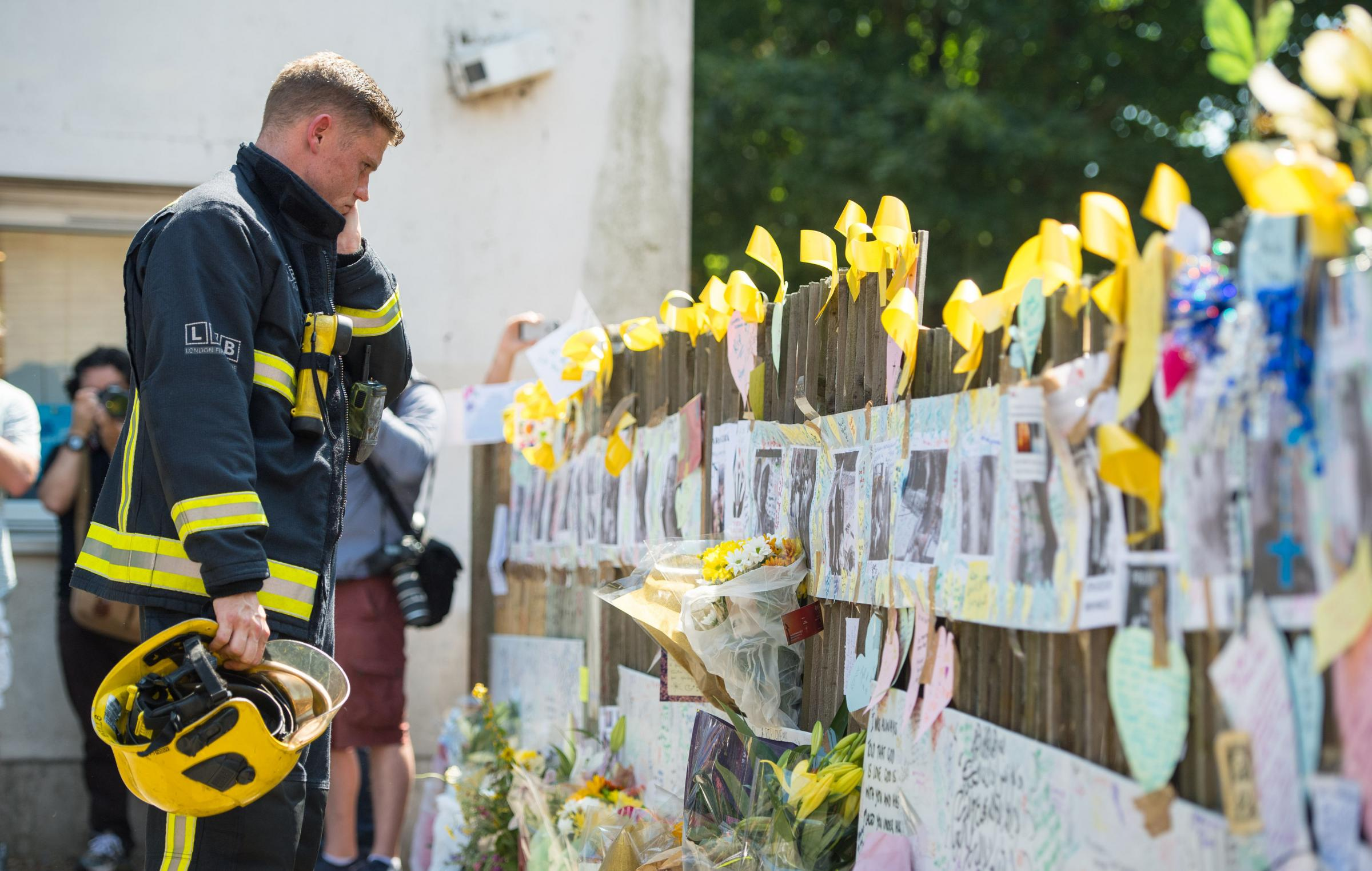A firefighter views tributes after observing a minute's silence at Latymer Community Centre, near to Grenfell Tower in west London, five days after the fire.Picture: Dominic Lipinski/PA Wire.