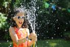 Nine year old Genevieve Mearns cools off with the help of a garden hose